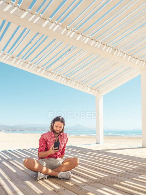 Bearded man browsing smartphone while sitting in gazebo on sandy beach near sea on sunny day — Stock Photo
