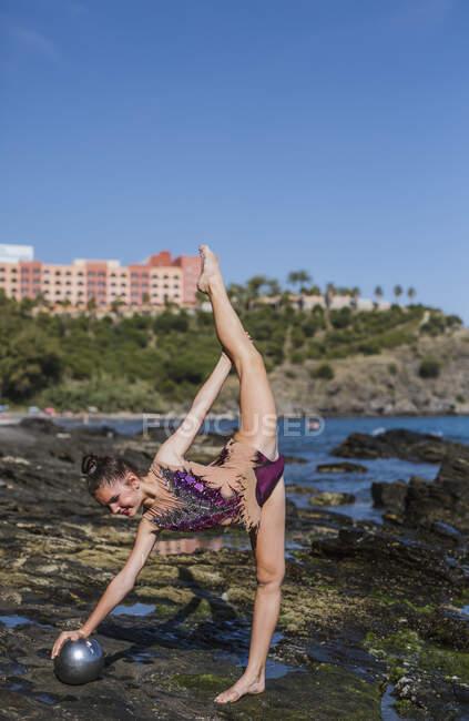 Женская гимнастка, сидящая на скалах и практикующая — стоковое фото
