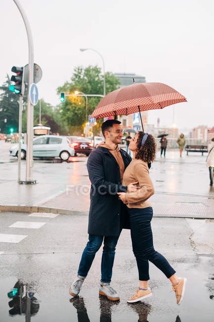 Seitenansicht von fröhlichen jungen Mann und Frau mit Regenschirm umarmen und einander anschauen, während sie auf der Straße stehen — Stockfoto