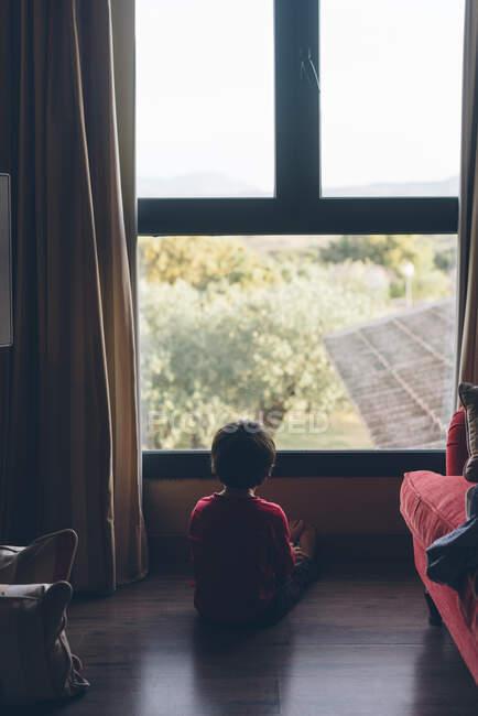 Vista trasera del niño de ensueño sentado en el suelo en la sala de estar y mirando hacia otro lado en la ventana - foto de stock