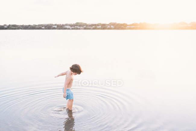 Vista posteriore del ragazzo sognante che cammina creando increspature in acque poco profonde della spiaggia contro la luce del tramonto — Foto stock
