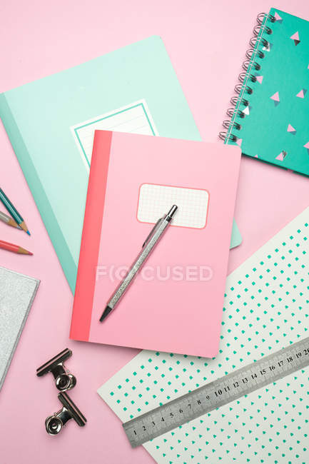 Composition of colorful notebooks, pen, pencils, ruler and paper clips arranged on pink desk — Stock Photo