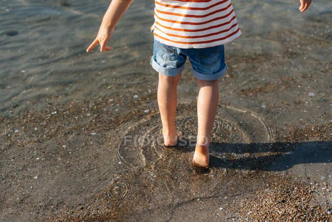 Пригадую собі маленького хлопчика, що бавився на мілководді, ступаючи вперед сонячним світлом. — стокове фото