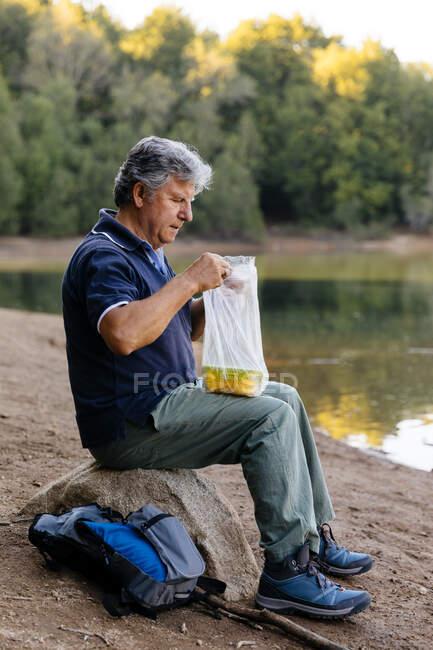Vue latérale de l'homme se préparant à manger des fruits dans la forêt — Photo de stock