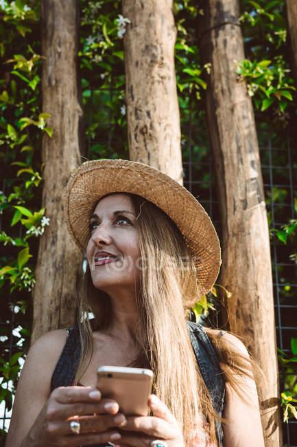 Lächelnde erwachsene Frau mit Strohhut, Smartphone in der Hand und wegschauend gegen grüne Bäume — Stockfoto