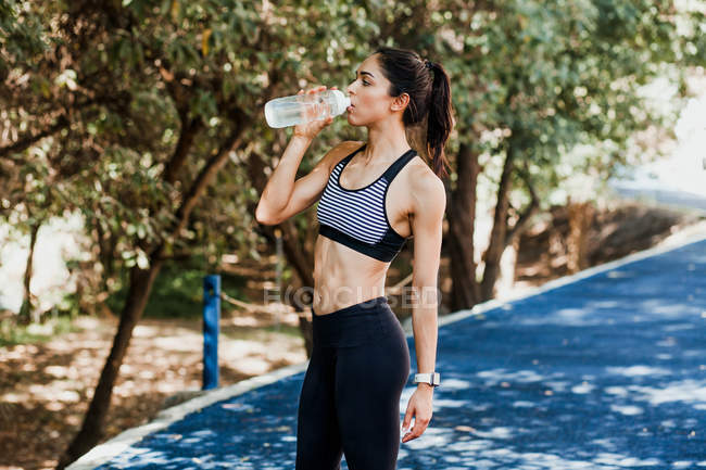 Mulher apto em sportswear água potável de garrafa em pista de corrida no dia de verão — Fotografia de Stock
