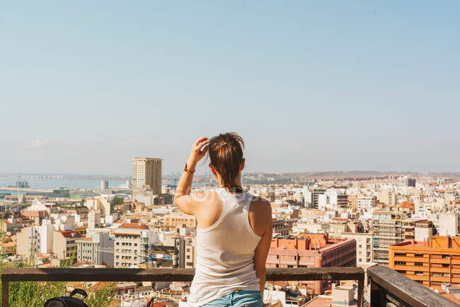 Woman on balcony looking at city views from above — Stock Photo