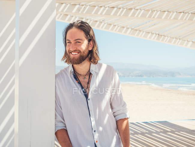 Красивий бородатий чоловік дивиться геть, спираючись на стовп білої альтанки на піщаному пляжі — стокове фото
