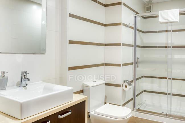 Interno del bagno in stile minimalista moderno decorato da piastrelle bianche con cabina doccia — Foto stock
