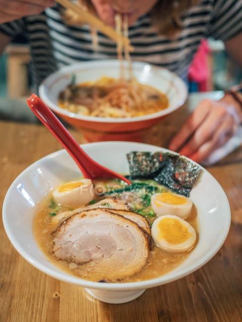 Обрезанный вид женщины, сидящей за деревянным столом и наслаждающейся миской вкусного рамэна, увенчанного яйцом и нарезанной свининой — стоковое фото