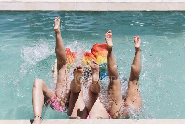 Dall'alto gambe di donne scalze in costume da bagno con bandiera LGBT e cadere in piscina sul resort — Foto stock