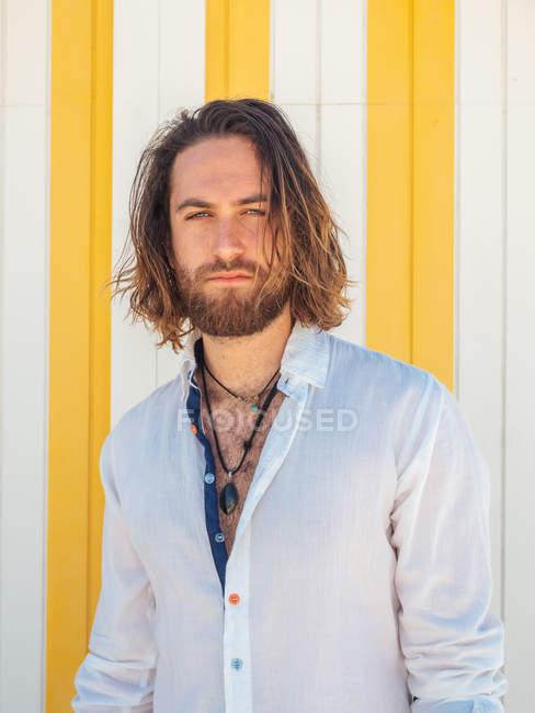 Hombre barbudo de confianza en traje casual contra la pared rayada en el resort - foto de stock