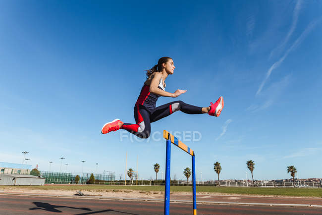 Strong young woman in sportswear leaping over hurdle against blue sky during workout on stadium — Stock Photo