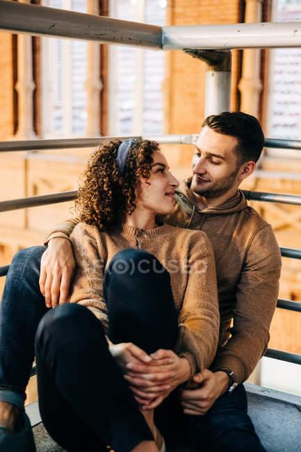 Jóvenes alegres abrazándose y mirándose unos a otros mientras se sentaban dentro del pabellón iluminado durante la fecha. - foto de stock