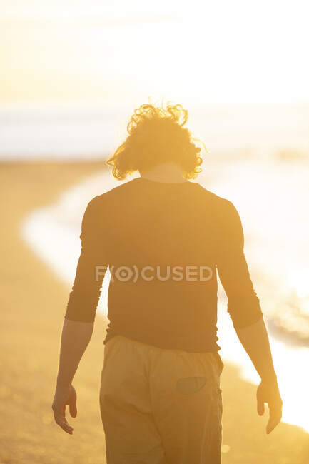 Thoughtful young man walking on the sand beach in sunset evening — Stock Photo