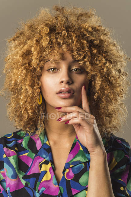 Portrait of attractive retro woman with curly hair on brown background — Stock Photo