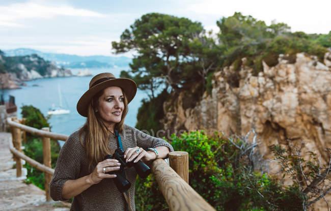 Femme souriante tenant binoculaire tout en se tenant à la clôture sur le trottoir de pierre sur le bord de la mer — Photo de stock