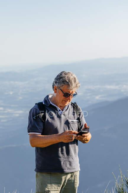 Старший использует свой мобильный телефон в горах — стоковое фото
