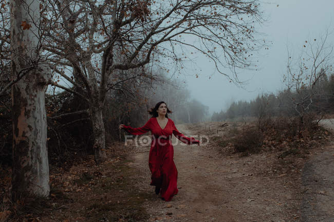 Dreamy woman in red dress walking along empty road of hazed mysterious terrain — Stock Photo