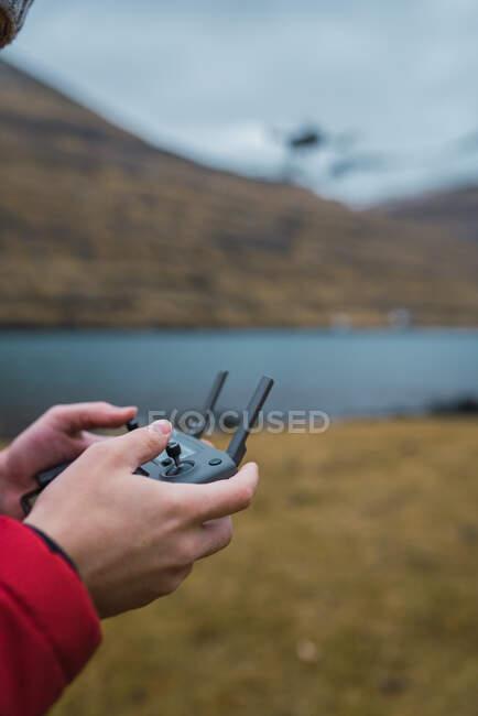 Unrecognizable person controling drone near lake in Faroe island — Stock Photo