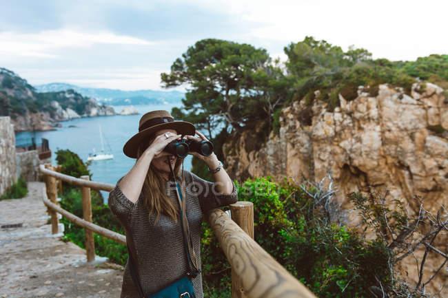 Mujer observando vista con binocular mientras está de pie en la valla en la pasarela de piedra en la orilla del mar - foto de stock