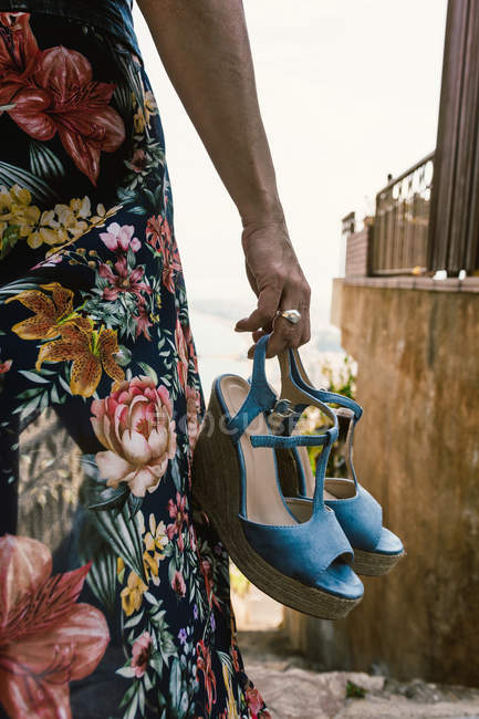 Closeup of woman in floral dress holding fashionable blue wedge heels standing on street — Stock Photo