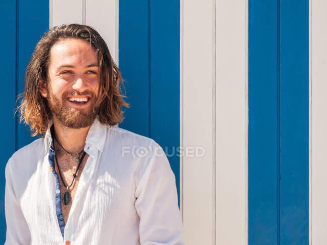 Hombre barbudo alegre en traje casual de pie contra la pared rayada en el recurso - foto de stock