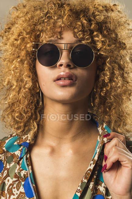 Портрет привабливою ретро жінка з Кучеряве волосся в стильних сонцезахисних окулярів — стокове фото