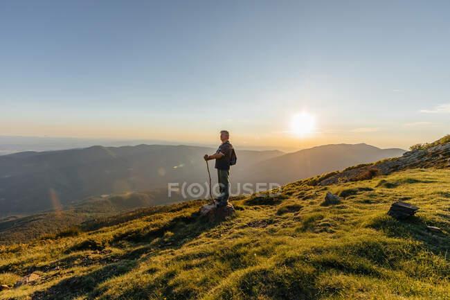 Vista laterale di un anziano con zaino e bastone di legno escursionismo attraverso la montagna — Foto stock