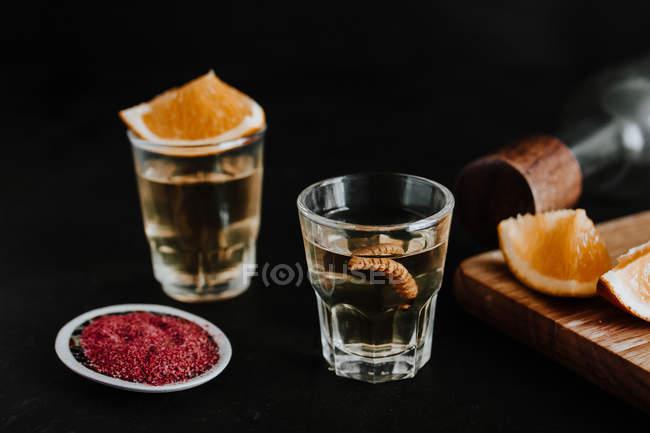 Выстрелы из традиционного мексиканского мескала, подаваемого с личинками и цитрусовыми на черном фоне — стоковое фото