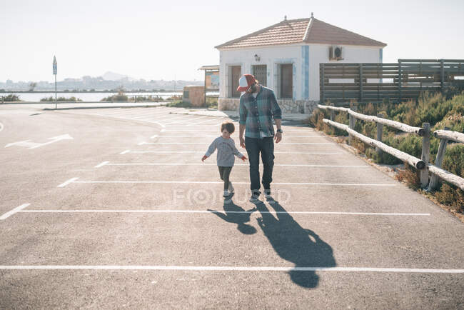 Hombre adulto con hijo juguetón en ropa casual caminando en el estacionamiento de la calle bajo el sol - foto de stock