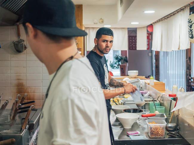 Vista lateral de los hombres jóvenes multirraciales cocinar plato japonés llamado ramen en el restaurante asiático y mirando en cámara - foto de stock