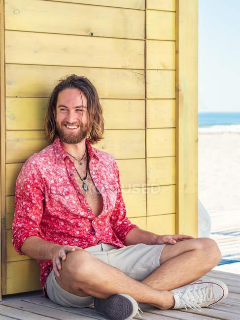 Homem barbudo alegre em roupa casual sentado contra a parede amarela no resort — Fotografia de Stock