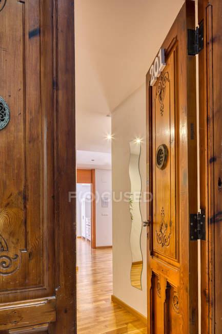 Interno di grande appartamento moderno attraverso porte aperte in legno decorate con intaglio — Foto stock