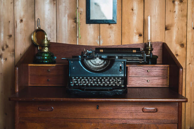 Vintage typewriter in a wooden old furniture in a wooden room — Stock Photo