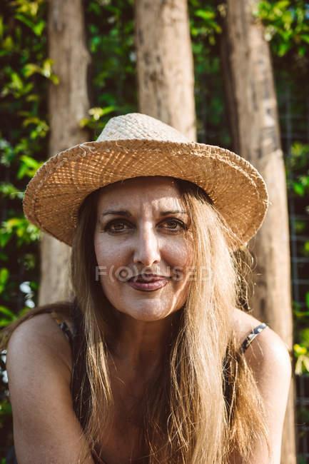 Contenuto donna adulta in cappello di paglia estivo seduta contro alberi verdi — Foto stock