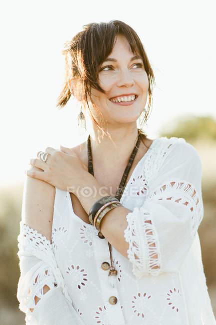 Retrato de mulher feliz em roupas brancas em pé ao ar livre à luz do dia — Fotografia de Stock