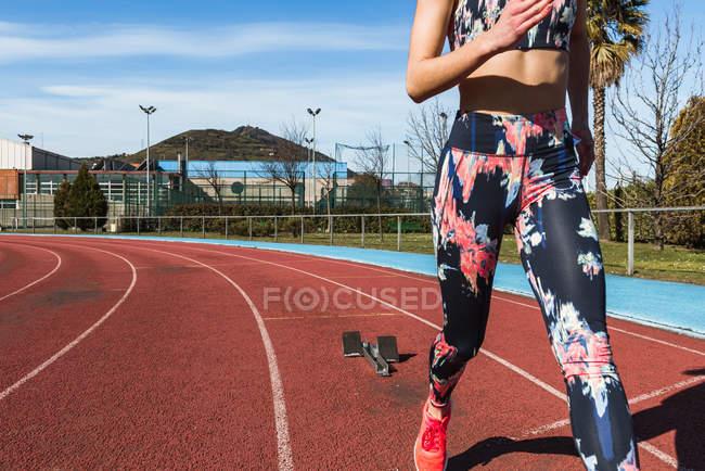 Крупный план сильной спортсменки в спортивной одежде, быстро бегущей против голубого неба в солнечный день на стадионе — стоковое фото