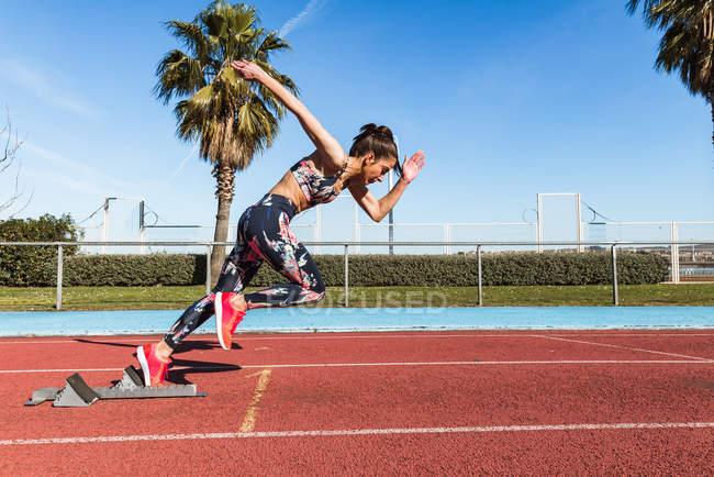 Сильная спортсменка в спортивной одежде быстро бегает против голубого неба в солнечный день на стадионе — стоковое фото
