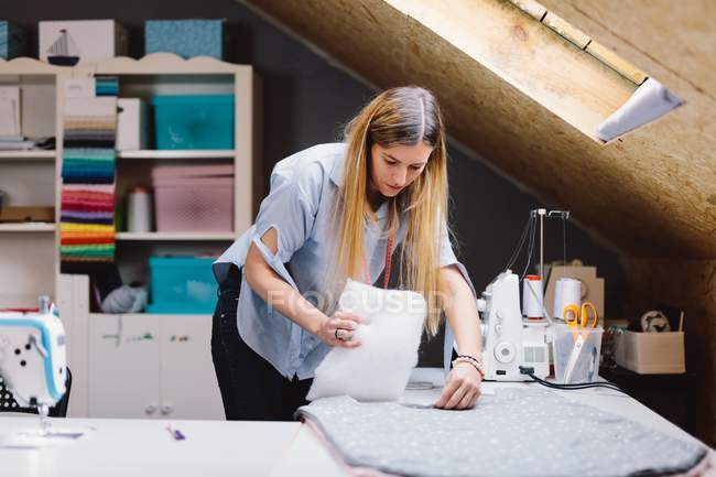 Woman filling handmade cushion with soft sintepon while working in attic atelier — Stock Photo
