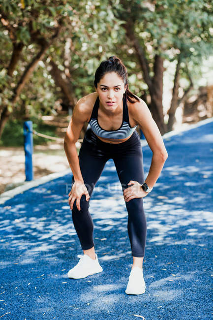 Fit woman in sportswear standing in resting pose on running track on summer day — Stock Photo