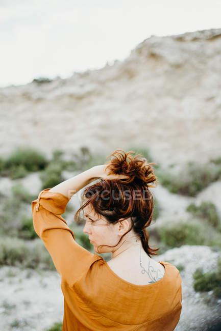 Femme réfléchie en chemisier avec la main dans les cheveux sur fond de désert sauvage paysage — Photo de stock