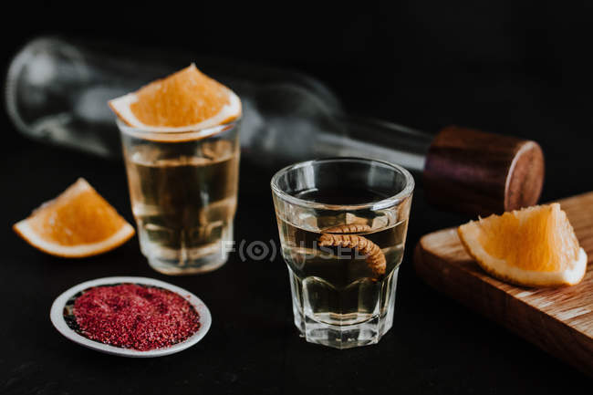 Shots of traditional Mexican mezcal served with larva and citrus on black background — Stock Photo