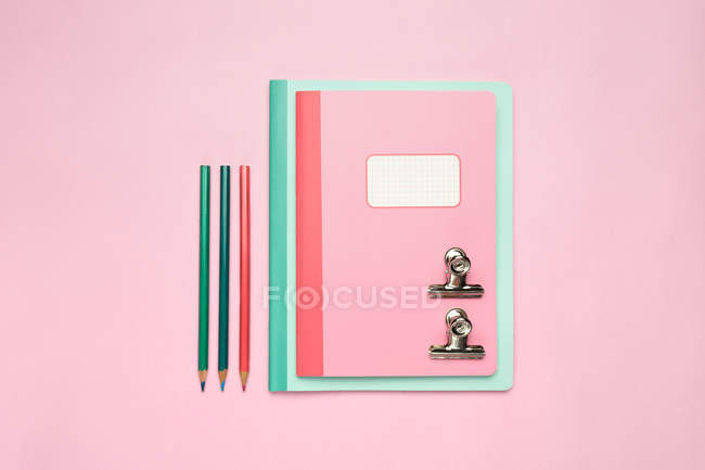 Composition of colorful notebooks, pencils and arranged on pink desk — Stock Photo