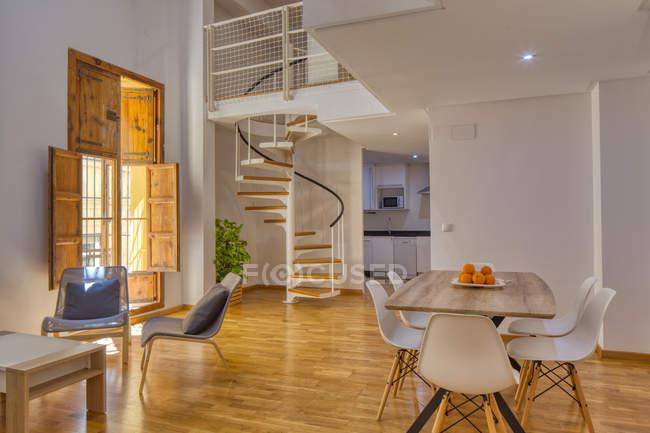 Interior de comedor sencillo y elegante y escaleras en moderno piso dúplex a la luz del día - foto de stock
