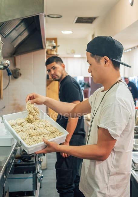 Вид сбоку на молодых людей разных рас, которые берут лапшу из травы для приготовления рамен в ресторане — стоковое фото