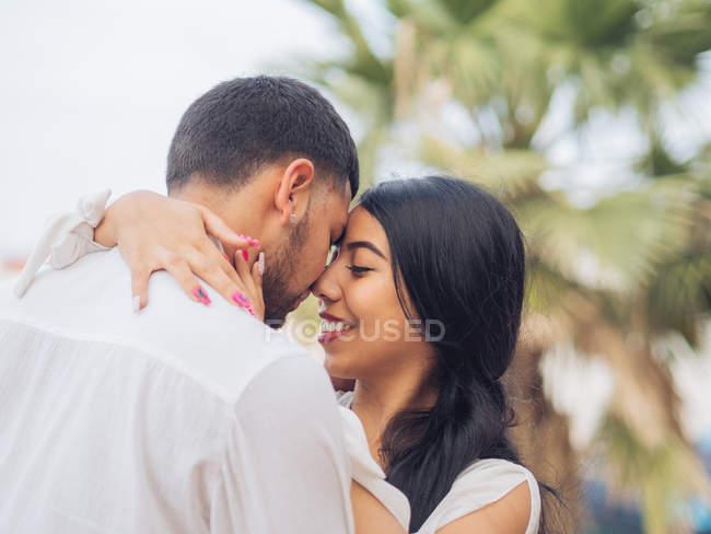 Вид сбоку симпатичной молодой пары в легкой одежде, обнимающейся с любовью и нежностью на причале в порту — стоковое фото