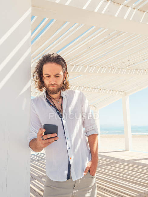 Hombre barbudo guapo usando teléfono inteligente mientras se apoya en el pilar de gazebo blanco en la playa de arena - foto de stock