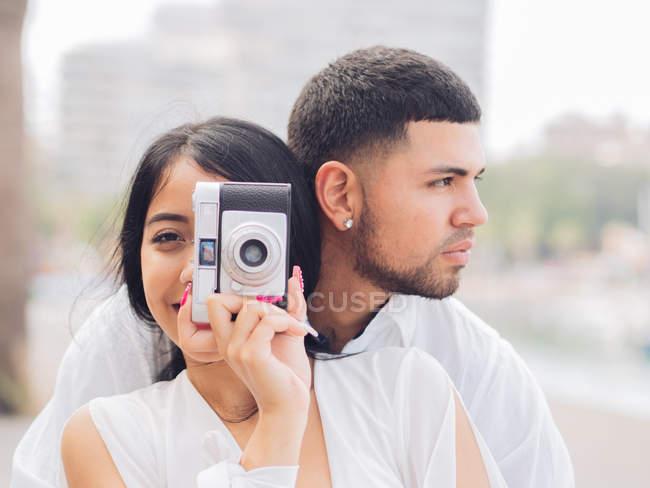 Jovem casal sentado e se divertindo tirando foto no banco de madeira à beira-mar arenoso — Fotografia de Stock