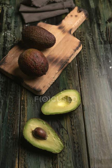 Aguacates frescos enteros y cortados a la mitad sobre mesa de madera - foto de stock